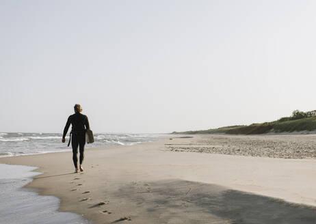 Lithuania, Nida, surfer walking in the beach - AHSF00723
