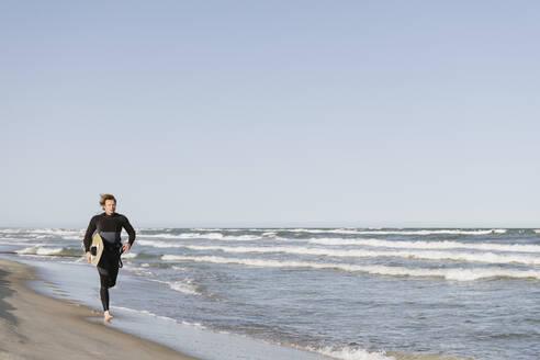 Surfer running at the beach - AHSF00726