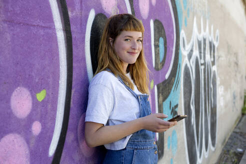 Smiling young woman using smartphone in front of purple graffiti wall - FLLF00250