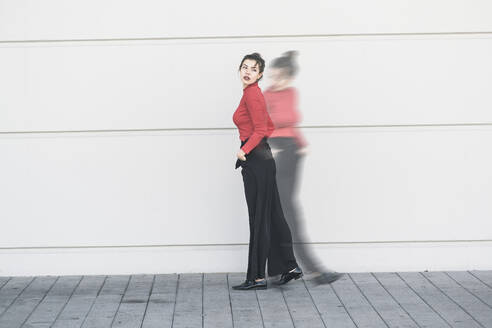 Digital composite of young woman moving in front of a wall - UUF18351