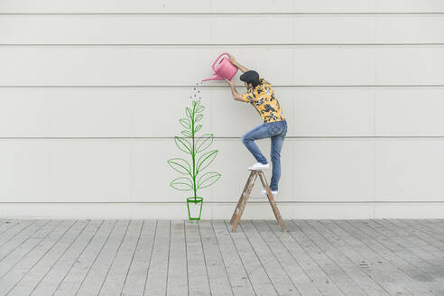 Digital composite of young man watering flower at a wall - UUF18357