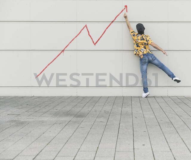 Digital composite of young man drawing a line graph at a wall - UUF18360 - Uwe Umstätter/Westend61