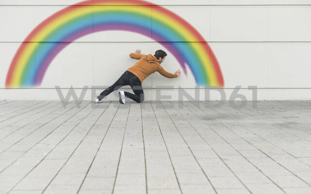 Digital composite of young man painting a rainbow at a wall - UUF18363 - Uwe Umstätter/Westend61