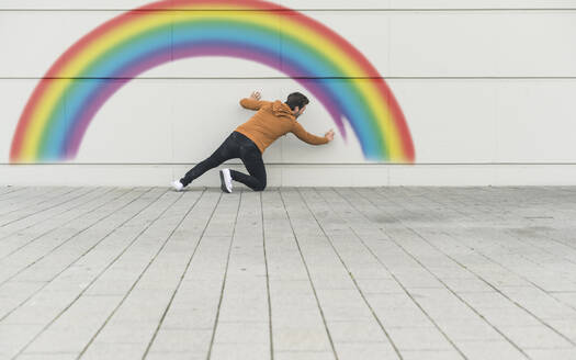 Digital composite of young man painting a rainbow at a wall - UUF18363