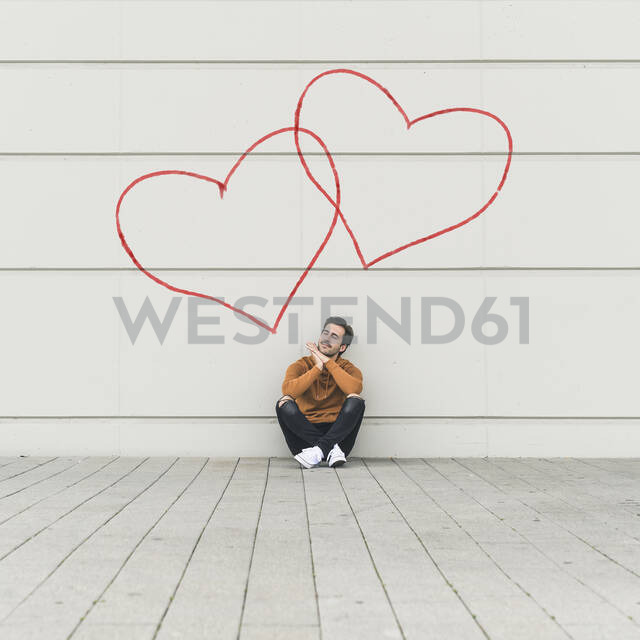 Digital composite of young man sitting at a wall with hearts - UUF18366 - Uwe Umstätter/Westend61