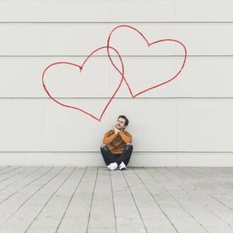 Digital composite of young man sitting at a wall with hearts - UUF18366