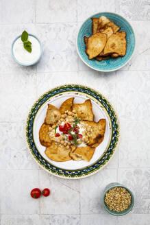 Fatteh (levantinisches Gericht, Frühstück oder Zwischenmalzeit, Mezze) geröstetes, in Stücke zerbrochenes Fladenbrot, Minz-Joghurt, Kichererbsen, Olivenöl, Tomate und Tahin - LVF08212