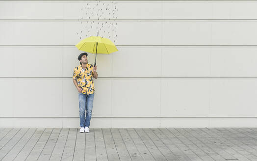 Digital composite of young man holding an umbrella at a wall with raindrops - UUF18369