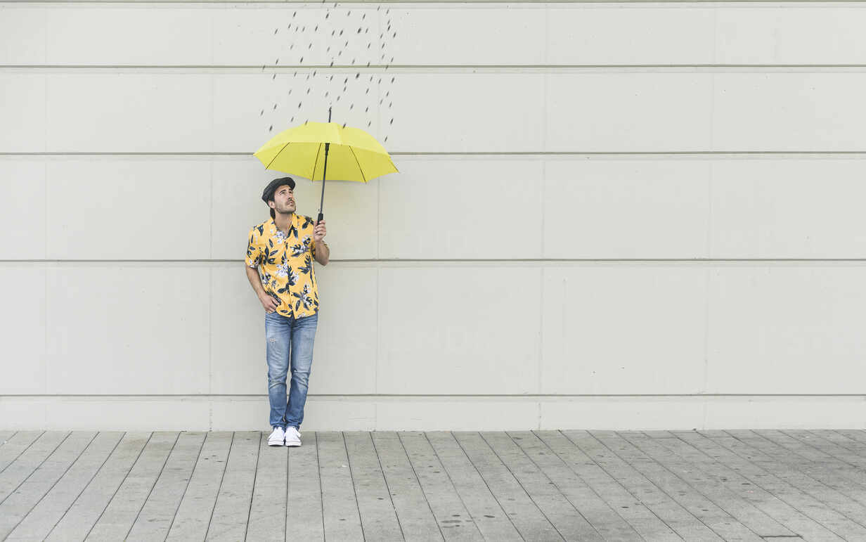 Digital composite of young man holding an umbrella at a wall with raindrops - UUF18369 - Uwe Umstätter/Westend61
