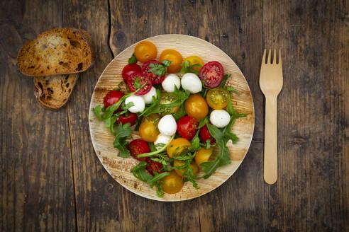 Salat mit Ruccola, Mozarella, Tomaten und Basilikum - auf umweltfreundlichem Einweggeschirr aus Palmblättern, Holzgabel - LVF08222
