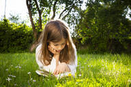 Girl lying on a meadow reading a book - LVF08226