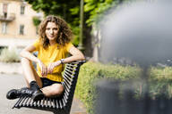 Portrait of confident young woman sitting on a bench - GIOF06994