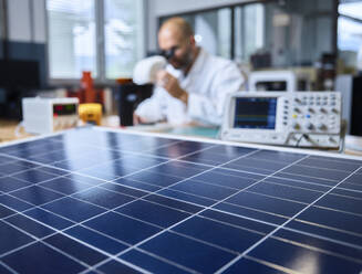 Solar panel and technician with microscope in background - CVF01395
