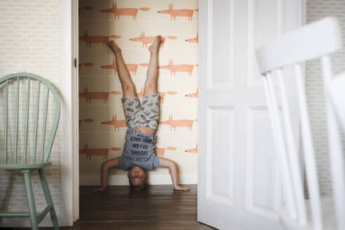 Russia, Moscow, boy staying on the head in the room - EYAF00318