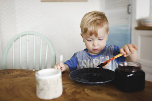 Russia, Moscow, cute little boy eating blueberry jam - EYAF00321