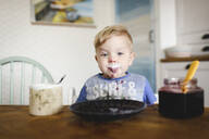 Portrait of cute little boy with blueberry jam in his face - EYAF00327