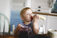 Cute little boy eating banana with blueberry jam in the kitchen - EYAF00333