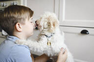 Boy playing with his dog at home - EYAF00336