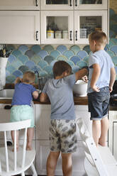 Three brothers cooking pancakes in the kitchen - EYAF00342