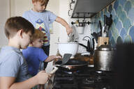 Three brothers cooking pancakes in the kitchen - EYAF00345