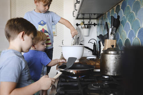 Russia, Moscow, three brothers cooking pan-cakes in the kitchen - EYAF00345