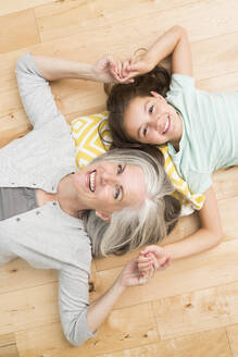 Caucasian grandmother and granddaughter laying on floor - BLEF12560