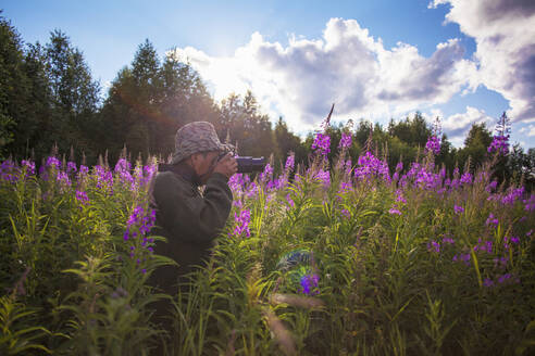 Mixed race photographer photographing flowers - BLEF12659
