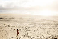 Caucasian girl standing with arms outstretched on beach - BLEF12761