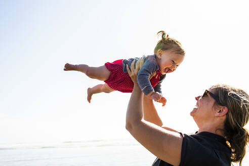 Caucasian mother lifting baby daughter on beach - BLEF12764