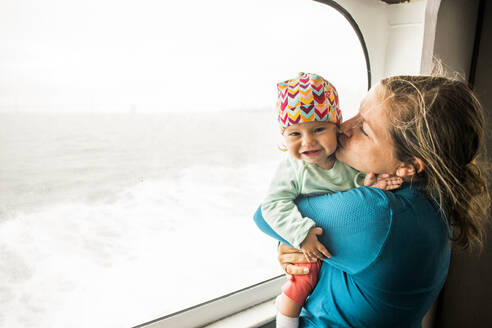 Caucasian mother kissing baby daughter at window - BLEF12770