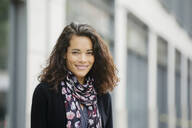 Mixed race woman smiling in city - BLEF12782