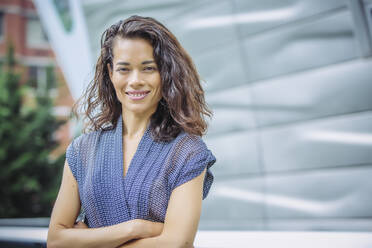 Mixed race businesswoman standing with arms crossed outdoors - BLEF12803