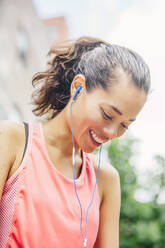 Indian athlete listening to earbuds - BLEF12821