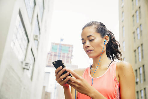 Mixed race athlete listening to mp3 player in city - BLEF12833