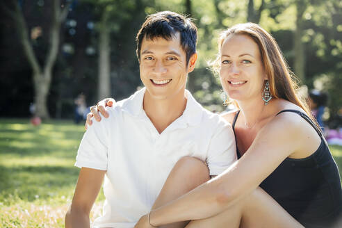 Smiling couple sitting on grass in park - BLEF12869