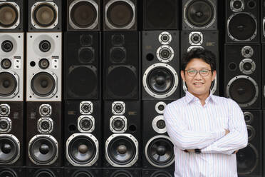 Asian man standing by stacked speakers - BLEF12941