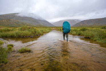Mari backpacker walking in remote stream - BLEF12974