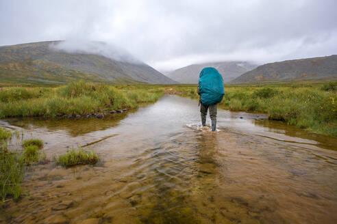 Mari backpacker walking in remote stream - BLEF12974