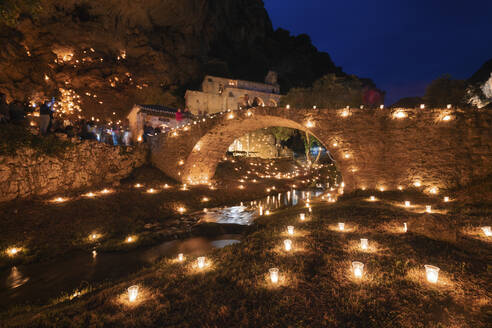 Medieval bridge over river surrounded by lit candles in town at night, Burgos Province, Spain - DHCF00197