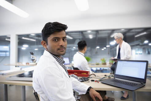 Portrait confident male engineer working at laptop in laboratory - HEROF37361