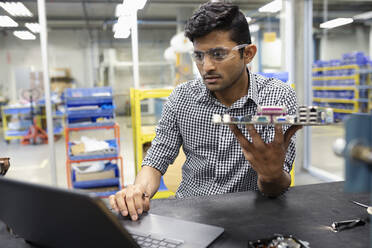 Focused male engineer assembling circuit board at laptop in research lab - HEROF37394