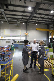 Machinists and supervisor talking in factory - HEROF37433