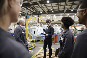 Female supervisor talking with machinists in factory - HEROF37463