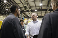Male supervisor shaking hands with machinists in factory - HEROF37466