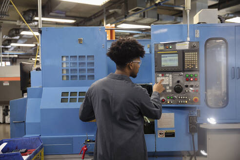 Male machinist operating machinery in factory - HEROF37478