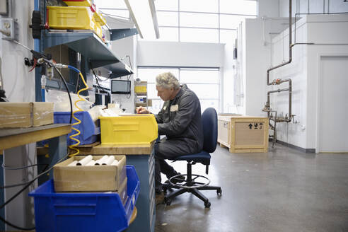 Male machinist working at desk in factory - HEROF37502