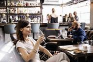 Smiling, confident businesswoman drinking wine in bar - HEROF37691