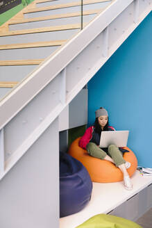 Young creative businesswoman using laptop on bean bag chair - HEROF37775