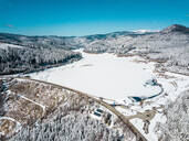 Aerial view of snow covered landscape against blue sky, Carinthia, Austria - DAWF00890