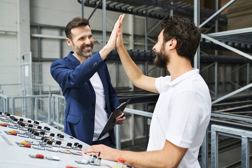 Happy businessman and employee high fiving at control panel in a factory - BSZF01149